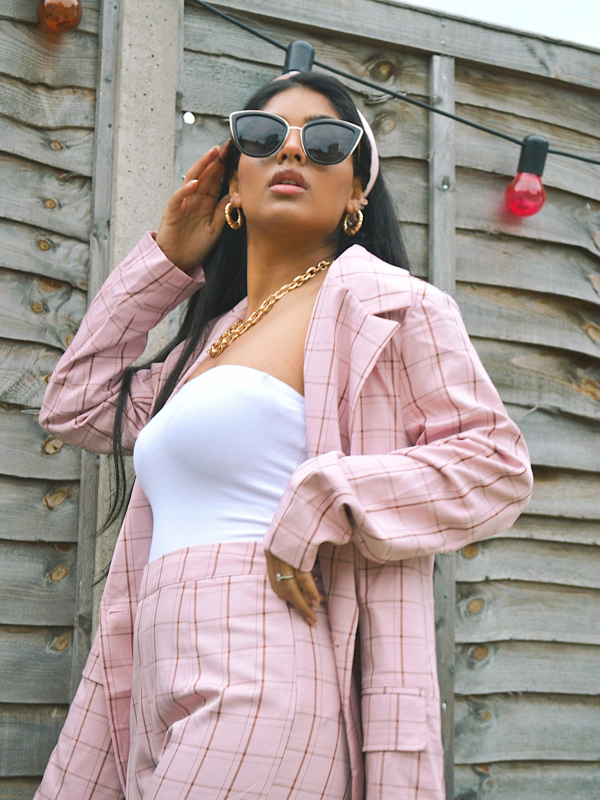 A brown blogger sharing her tips on how she style chic outfits, dressed in a pink checked pant suit.