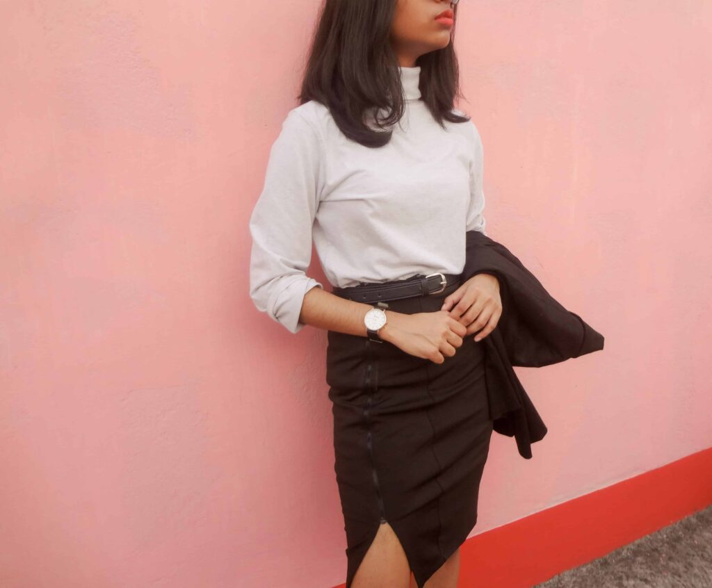 Black skirt and blazer paired with a neutral turtleneck in grey colour, one of the most trendy wardrobe basics.