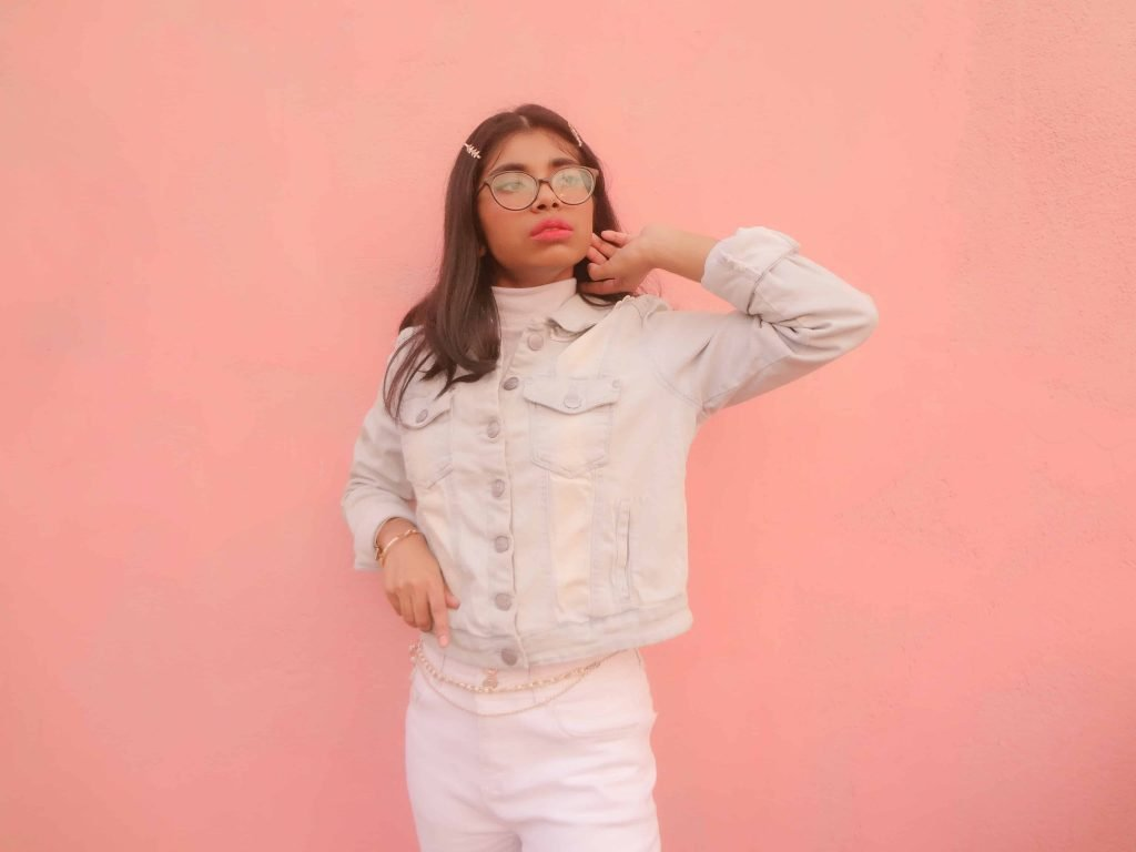A petite fashion blogger in front of a peach background in a cropped denim jacket and high-rise jeans sharing how to look tall without heels.