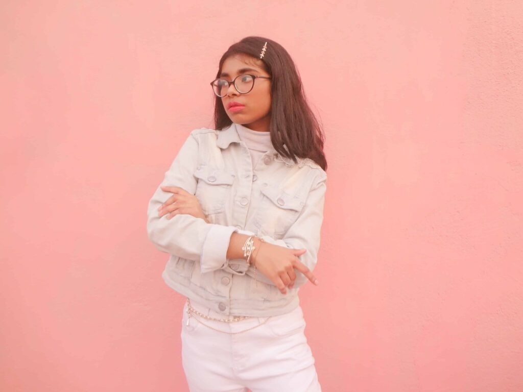 petite fashion blogger in front of a peach background in a cropped denim jacket and high-rise jeans sharing how to look tall without heels.