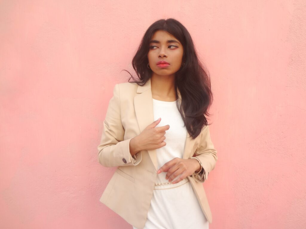 A style blogger showcasing the best of kfashion in a white dress layered under a beige blazer with shoulder pads, a trendy wardrobe basics.
