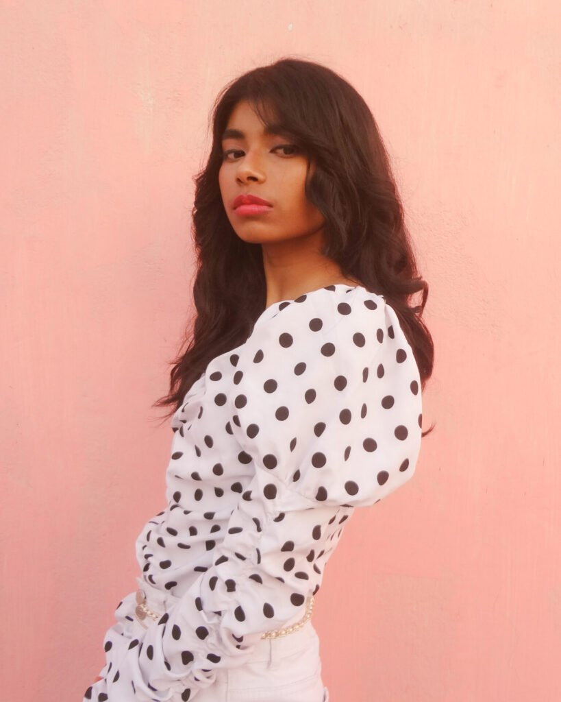 An India-based fashion blogger and gen z content creator posing in a polka dot top in front of a pink wall.