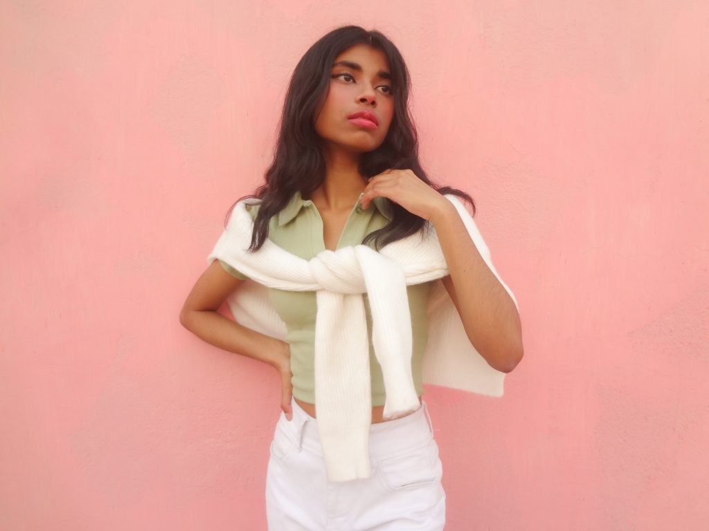 a brown fashion blogger on how to style pastels with neutrals in front of a pink wall.